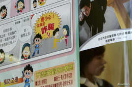 A person walks past an anti-scam poster in Taipei, (File photo).