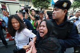 A friend, center, tries to help as an anti-coup protester, left, is detained by a Thai police officer during a protest on a street in Bangkok, Thailand Saturday, May 24, 2014.