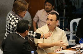 FILE - Philippine Senator Leila de Lima, center, Chairperson of the Commitee on Justice and Human Rights, tries to pacify an argument between Senator Allan Peter Cayetano, right, and Senator Antonio Trillanes IV as they question a former Filipino mil