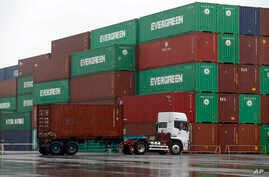 FILE - A truck leaves a container terminal in Tokyo, Japan.