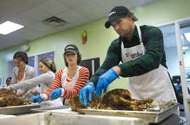 Washington Nationals baseball infielder Ryan Zimmerman, right, and his wife Heather, center, help pack turkeys for Thanksgiving meals at Food & Friends Food & Friends in Washington, Nov. 23, 2015.