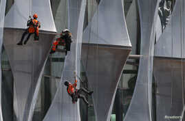 FILE - Construction workers climb a new building in the Nine Elms area of London, Britain, April 11, 2017.