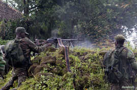 A Congolese soldier shoots in the direction of M23 rebels from their position near the Rumangabo military base in Runyoni, 58 km (36 miles) north of Goma, Oct.31, 2013.