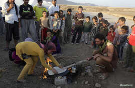 Displaced people from the minority Yazidi sect, who fled the violence in the Iraqi town of Sinjar, make bread at Bajed Kadal refugee camp south west of Dohuk province, Aug. 15, 2014.