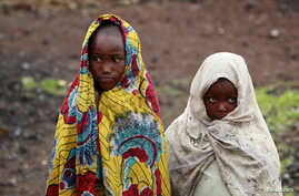 Girls, displaced by recent fighting between Congolese army and the M23 rebels, cover themselves from the cold in Munigi village near Goma in the eastern Democratic Republic of Congo September 1, 2013.