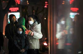 Commuters wearing protection masks, wait for buses at a bus station on a heavy polluted day in Beijing, China, Jan. 2, 2017.