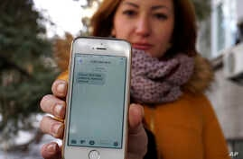 """FILE - Television journalist Julia Kirienko holds up her smartphone to show a text message reading """"Ukrainian soldiers, they'll find your bodies when the snow melts,"""" in Kyiv, Ukraine, Feb. 22, 2017."""