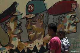 People walk in front of a wall sprayed with stencilled paintings depicting the Egyptian military council members in Tahrir Square in Cairo May 24, 2012.
