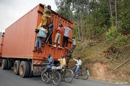 Young people on bicycles hang to the back of a truck outside the capital Bujumbura, Burundi, July 19, 2015.