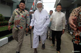 Abu Bakar Bashir, center, the alleged mastermind of the 2002 Bali bombings, walks as he is visited by Yusril Ihza Mahendra, right, who is the lawyer of Indonesia's presidential candidate Joko Widodo, at Gunung Sindur prison in Bogor, Indonesia, Jan.