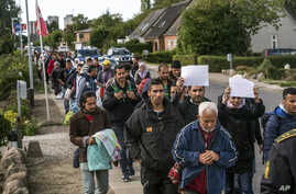 Middle Eastern migrants, who came from Germany by ferry and train Sunday night, and are walking  from Rodby in southern Denmark toward Sweden, Sept. 7, 2015.
