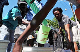 Haitian earthquake victims struggle to get water from a distribution team in Port-au-Prince on 18 Jan 2010