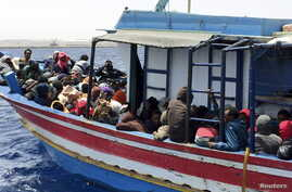 Illegal migrants who attempted to sail to Europe, sit in a boat carrying them back to Libya, after their boat was intercepted at sea by the Libyan coast guard, at Khoms, Libya May 6, 2015. Libya's coast guard detained on Wednesday almost 600 illegal