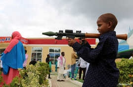 FILE - A Somali boy plays with a toy model of a rocket-propelled grenade (RPG) in Mogadishu, July 6, 2016. Children have been maimed and killed playing with real weapons, ordnance and explosive devices.