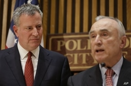 New York City Mayor Bill de Blasio, left, listens while Police Commissioner Bill Bratton speaks during a news conference at police headquarters in New York, Dec. 22, 2014.