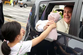 In this picture made available by the Vatican newspaper L'Osservatore Romano, Pope Francis receives a bouquet of flowers from a child as he leaves in a car in Seoul at the end of his five-day visit to South Korea, Monday, Aug. 18, 2014. Pope Francis