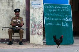 A Sri Lankan police officer guards outside a polling station before the beginning of voting in Jaffna, Sri Lanka, Saturday, Sept. 21, 2013.