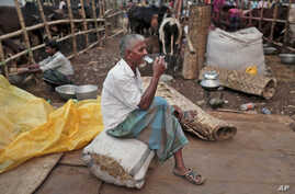 A Bangladeshi trader smokes a cigarette as he waits for customers at a temporary cattle market for the upcoming Eid al-Adha festival in Dhaka, Bangladesh, Oct. 1, 2014.