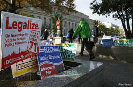 Pedestrians pass by a DC Cannabis Campaign sign in Washington, Nov. 4, 2014.  Voters in the U.S. capital and two West Coast states will decide whether to legalize marijuana in a test for broader cannabis legalization efforts across the United States....