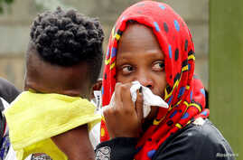 Relatives grieve after learning a loved one was killed in an attack on an upscale hotel compound, in Nairobi, Kenya, Jan. 16, 2019.