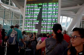 FILE - a flight information board shows cancelled flights due to smoke from Mount Agung at the Ngurah Rai International Airport in Bali, Indonesia.