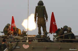 Israeli soldiers stand on an armoured personnel carrier (APC) outside the central Gaza Strip as they fire mortar shell towards Gaza before a ceasefire was due, early August 1, 2014. Israeli shelling near the southern Gaza town of Rafah killed at leas