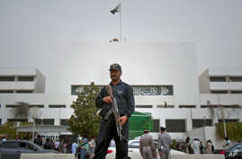 A Pakistani police commando stands guard at Parliament House in Islamabad, Pakistan, March 20, 2012 file photo.