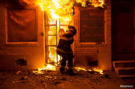 A firefighter uses a saw to open a metal gate while fighting a fire in a convenience store and residence during clashes after the funeral of Freddie Gray in Baltimore, Maryland in the early morning hours, April 28, 2015.