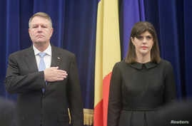 FILE - Romanian President Klaus Iohannis and the Chief of anti-corruption prosecuting agency DNA, Laura Codruta Kovesi, stand while listening to the national anthem being played at the beginning of the anti-corruption agency's annual report, in Bucha