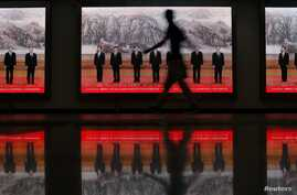 A pedestrian walks past electronic signs displaying pictures of China's Politburo Standing Committee members at a subway station, Shanghai, June 18, 2013.