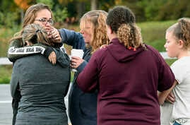 Friends of victims who died in Saturday's fatal limousine crash comfort each other after placing flowers at the intersection in Schoharie, New York, Oct. 7, 2018.