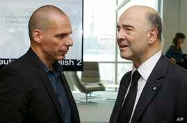 Greek Finance Minister Yanis Varoufakis, left, and Commissioner for Economic and Financial Affairs, Taxation and Customs, Pierre Moscovici speak at the Informal Meeting of Ministers for Economic and Financial Affairs of the EU in Riga, Latvia, Apr. 2