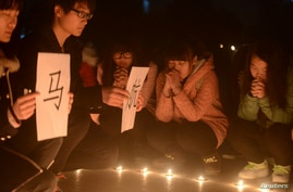 FILE - College students hold placards near lit up candles as they pray for passengers of the missing Malaysia Airlines MH370 plane in Yangzhou, Jiangsu province.