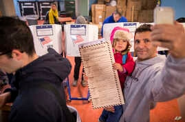 A man takes a selfie with his child as he waits to vote at a polling station in the Brooklyn borough of New York, Nov. 8, 2016.
