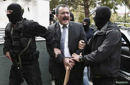FILE - Extreme-right Golden Dawn party senior lawmaker Christos Pappas is escorted by anti-terrorism police officers to a courthouse in Athens, Oct. 3, 2013.