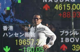A man is reflected on the electronic board of a securities firm in Tokyo, Jan. 15, 2016. Asian stock markets were mixed Friday as investors were reluctant to return to risky assets despite ebbing fear about the Chinese currency devaluations and Wall