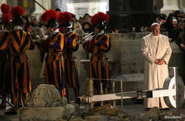 Pope Francis stands next to members of the Vatican Swiss guard band in St. Peter's Square at the Vatican, Dec. 31, 2016.