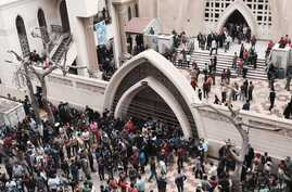 Relatives and onlookers gather outside a church after a bomb attack in the Nile Delta town of Tanta, Egypt, Sunday, April 9, 2017.