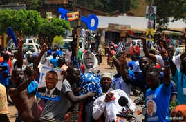 Supporters of Uganda's main opposition presidential candidate Kizza Besigye gesture while standing next to an effigy of him during a Feb. 10 campaign rally in Kampala.