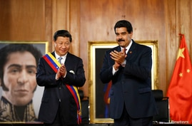 China's President Xi Jinping (L) claps with his Venezuelan counterpart Nicolas Maduro, at their meeting at Miraflores Palace in Caracas, July 20, 2014.