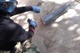 In this image taken from amateur video posted online, appearing to show a presumed UN staff member measuring and photographing a canister in the suburb of Moadamiyeh in Damascus, Syria, Aug. 26, 2013.