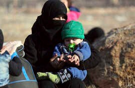 A Syrian woman and a child, who were evacuated from the Syrian city of Aleppo during the ceasefire, arrive at a refugee camp in Rashidin, near Idlib, Syria, Monday, Dec. 19, 2016.