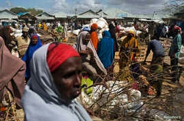 FILE - Somali refugees organize their collected ration of food during a distribution exercise outside a United Nations World Food Program center at a refugee settlement in Dadaab, Kenya, October 2013.