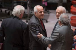 FILE - Palestinian U.N. Ambassador Riyad Mansour, center, greets fellow diplomats before a meeting of the U.N. Security Council in New York, July 28, 2014.