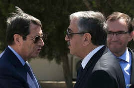 FILE - Cypriot President Nicos Anastasiades, left, and breakaway Turkish Cypriot leader Mustafa Akinci, right, talk at the disused Nicosia airport inside a United Nations controlled buffer zone in this divided island of Cyprus, Sept. 14 2016. The lea