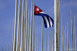 FILE - The Cuban flag flies in front of the U.S. Interests Section, background, in Havana, May 22, 2015.