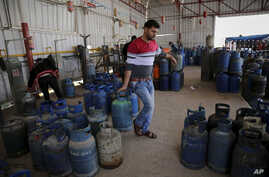 In this Thursday, Jan. 7, 2016 photo, a Palestinian worker carries a gas canister filled only by half, as other bottles wait to be filled at the main gas station in Jebaliya, Gaza Strip. Gas used for heating and cooking in Gaza is in short supply bec