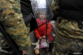 A migrant girl holds her toys as Macedonian policemen block migrants at the Greek-Macedonian borders, near the village of Idomeni, Greece Nov. 20, 2015.