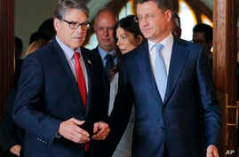 Russian Energy Minister Alexander Novak, right, welcomes U.S. Secretary of Energy Rick Perry for talks in Moscow, Russia, Sept. 13, 2018.