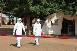 Health workers walk toward an area used for Ebola quarantine after they worked with Fanta Kone, 2, who died of the disease at an Ebola virus center in Kayes, Mali.